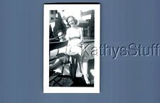 FOUND B&W PHOTO A_5037 PRETTY WOMAN IN SWIMSUIT SITTING ON CHAIR ARM BY MAN