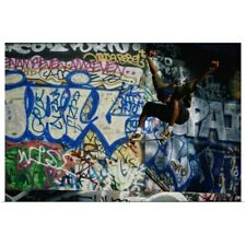 Poster Print Wall Art entitled Male skateboarder in mid-air, graffiti-covered