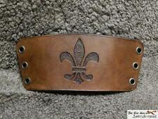 Hand-made carved leather bracers with fleur de lys motif, antique brown finish