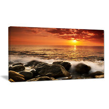 Design Art Bright Sunset over Rocky Shore Photographic Print on Wrapped Canvas